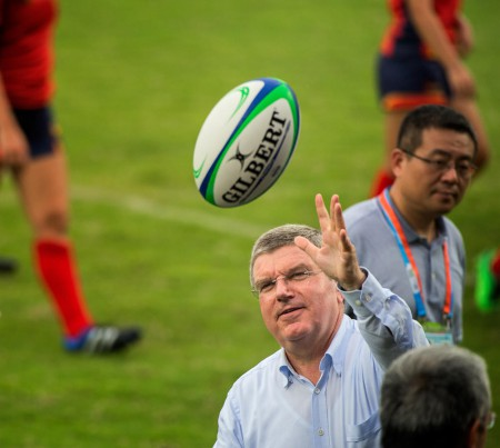 IOC president Tomas Bach plays with a rugby ball before the gold medal playoffs in Nanjing. Photo: Xinghua