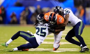 Julius Thomas (80) of the Denver Broncos is tackled by Richard Sherman (25) and Kam Chancellor in the 2013-14 Superbowl championship match. Photo: o