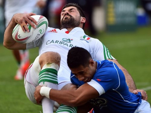 Italian fullback Andrea Masi is tackled by a Samoan player. Photo: Planet Rugby