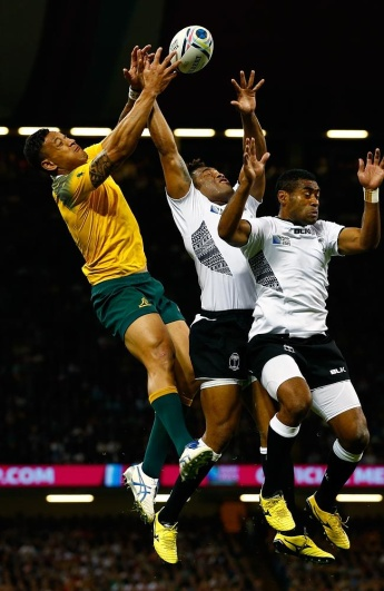 Wallaby Israel Folau (left) negates Fiji's Metuisela Talebula (centre) and Asaeli Tikjoirotuma's attempt to collect a high kick for a try. Photo: SMH